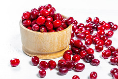 Ripe red cornel berries on a white table