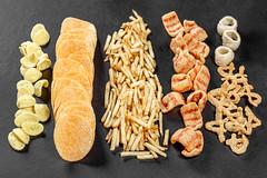 Set of potato snacks and chips on black background