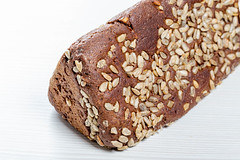 Black bread with sunflower seeds on white wooden background