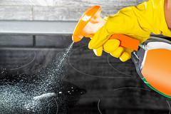 Hand in yellow household gloves with spray to clean the cooking surface