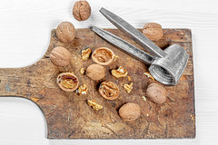 Whole and broken walnuts on an old wooden Board. Top view