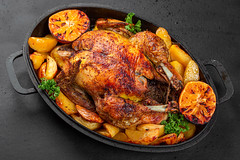 Baked chicken with potatoes and oranges on a baking sheet on a black background