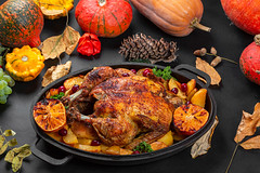 Baked chicken with potatoes, orange and dogwood berries. Background for autumn holidays
