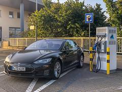 Schwarzer Tesla Model S lädt auf einem Parkplatz aus der Frontperspektive