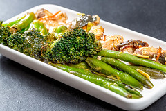 Close-up of asparagus and broccoli with pieces of fish on a white plate