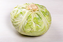 Green fresh raw cabbage on white wooden background