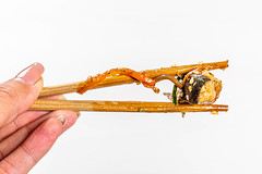 Piece tuna in sauce close up in chopsticks holding a woman on white background