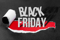 """Conceptual background to Black Friday. Black torn paper and the inscription """"black friday"""" on a red background"""