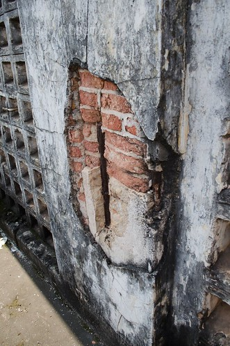 Rotten brick and weathered concrete pattern on facade of old cinema house in Cambodia (variation)