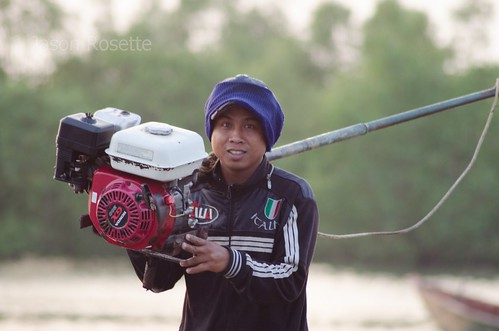 Fisherman carries his engine home at the end of the day in Cambodia