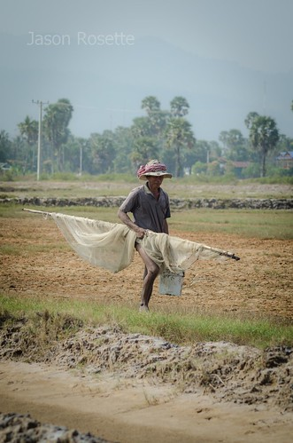 Man carries a fishing net out to the rice field in Cambodia