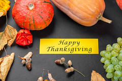 Happy thanksgiving wish on autumn background with pumpkins, grapes and dry leaves