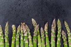 Fresh raw green asparagus on black background