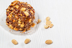 Cake with cocoa and roasted peanuts on a white wooden background
