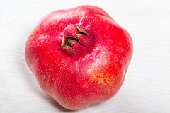 Pomegranate fruit on a white wooden background