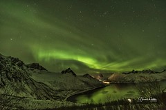 Aurora Boreal y reflejos verdes sobre Fjordgard Isla de Senja