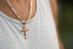 Golden crucifix pendant on a man's chest