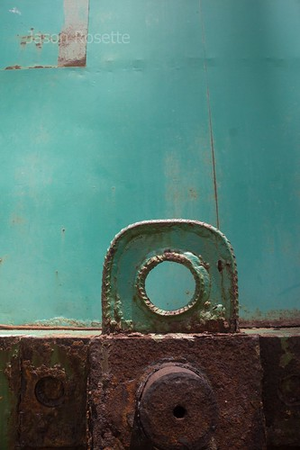 Metal Eyelet on Rusty Steel, with Green in Background