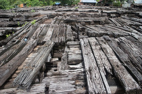 Rotten weathered wooden railroad ties stacked outside old station in Cambodia - wide view