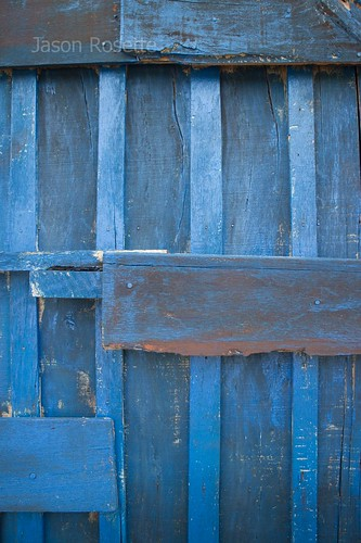 Weathered blue door and boards at train station, Cambodia (vertical)