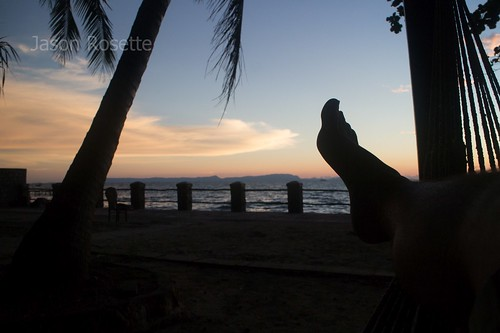 Holiday in sia: Silhouette of Foot and Hammock with Sea at Dusk