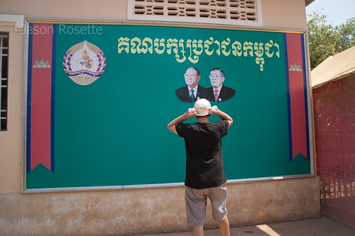 Foreign Man Stands in Front of Politcial Banner in Cambodia