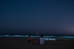 Two people on the beach watching stars above the sea