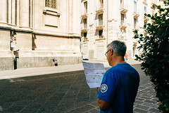 Tourist looking up directions on the map of Catania
