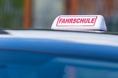 Weiß-roter Schild auf blauem Fahrschulauto