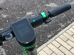 """Closeup of a Lime electric scooter with battery indicator and """"Scan to ride"""" on the display"""