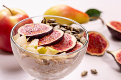 Close-up glass bowl of oatmeal with pieces of figs, pears, yogurt and pumpkin seeds