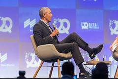 Ehemaligen US-Präsident Barack Obama sitzt im Talk der Startup-Konferenz in München auf einem Sessel auf der Bühne