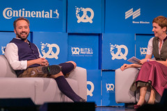 American entrepreneur Drew Houston smiles while being interviewed by Britta Weddeling in perfect Oktoberfest outfit at the Bits & Pretzels conference