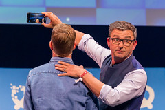 Actor Hans Sigl makes a video with his phone together with Joko Winterscheidt on the Center Stage of the founders' conference Bits19 in Munich