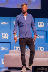 German presenter and actor Joko Winterscheidt standing on the stage at the founders' conference Bits & Pretzels 2019