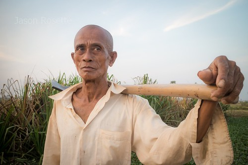 Medium view farmer holds his shovel at sunset in Siem Reap, Cambodia - he looks off screen