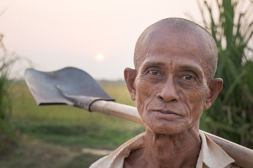 Close up view farmer holds his shovel at sunset in Siem Reap, Cambodia (#2)