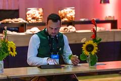 Frühstückspause auf der Bits & Pretzels Messe: Mann in bayrischer Tracht sitzt mit Brötchen an der Holzbar und nutzt das Tablet