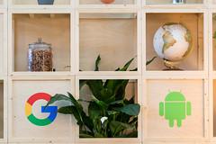 Holzregal mit Google und Android-Symbol, Globus und Brezeln im Glas