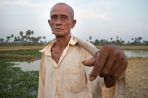 Medium view farmer holds his shovel at sunset in Siem Reap, Cambodia - hand in foreground