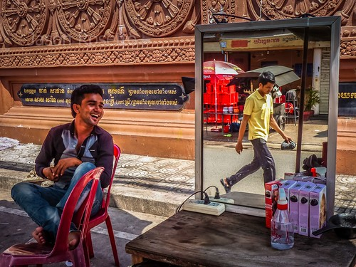 Barber in Phnom Penh laughs as he chats with a nearby Friend