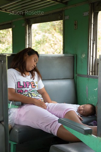 Mother and Child Sleep While Riding a Train in Thailand