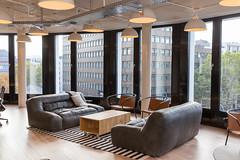 Lounge mit Sofas und großer Fensterfront mit Blick über Köln, vom Coworking-Büro WeWork