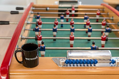 Foosball with black WeWork cup at the joint community area at the rental office in Cologne