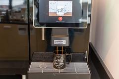 """Vollautomat-Kaffeemaschine Franke A800 gießt das Heißgetränk in eine """"Do what you love - WeWork"""" - Tasse"""
