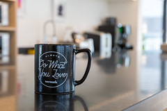 Black cup with coffee at a coworking office for independent entrepreneurs: Always do what you love by WeWork