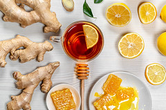 A Cup of tea with ginger root, fresh lemon and honey on a white wooden background. The view from the top