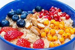 Breakfast background with oatmeal with almonds, sea buckthorn, strawberry, blueberry, pomegranate