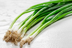 Fresh young onion white wooden background