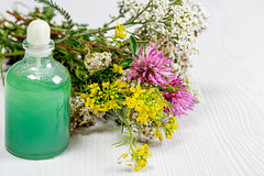 Bottle with green cosmetic and a bouquet of wild flowers on a white wooden background. The concept of natural cosmetics